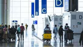 Travellers walk through the departures hall at the Hong Kong International Airport. T