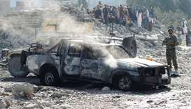 An Afghan National Army soldier inspects the wreckage of a burnt army car at the site of a blast