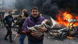 Civilians carry a young victim at the scene of an explosion in the town of Azaz in the northern coun