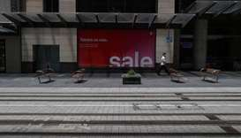 A lone person walks through a usually busy part of the city centre at lunch hour amidst the tighteni