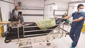 A nurse pushes a bed on which rests a Covid-19 patient at Rafic Hariri University Hospital Corona ER
