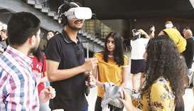 A group of Northwestern Qatar students using VR glasses to showcase their film projects.