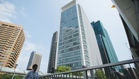 A pedestrian walks past the Ark Hills South Tower building, which houses the Takata Corp headquarter