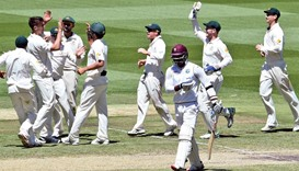 Australian bowler Mitch Marsh (second left) celebrates with teammates after dismissing West Indies b