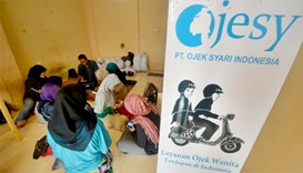 Female motorbike taxi drivers learning how to take orders from their smartphones at an office in Jak