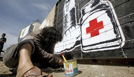 Artist Murad Subai paints graffiti depicting a bottle of water, medicine and a loaf of bread on a st