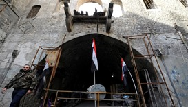 A member of forces loyal to Syria's President walks past Syrian national flags in the Old City of Al