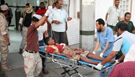 A wounded Yemeni man arrives at a hospital after a suicide bomber killed 50 soldiers
