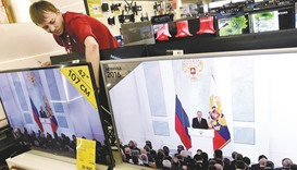 A shop assistant at an electronics store in Moscow works behind TV sets broadcasting Putin's state o