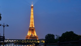 The lighted Eiffel Tower in front of the Seine river in front Beaugrenelle in Paris