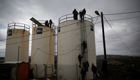 Israeli youths climb atop water tanks as they make preparations for an expected eviction in Amona