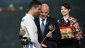 FIFA president Gianni Infantino (C) gives the Golden Ball trophy to Real Madrid's forward Cristiano