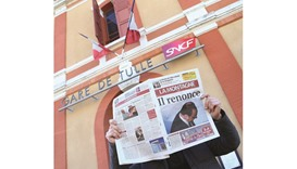 A man reads the French regional daily newspaper La Montagne, which had on its front page a portrait