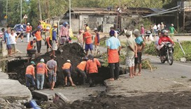 Workers inspect a road damaged by the  typhoon in Tabaco, Albay province yesterday.