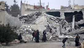 People stand near near rubble of damaged buildings in al-Rai town