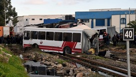 Tunisian security officers gather at the site of a collision, after a train slammed into a public bu