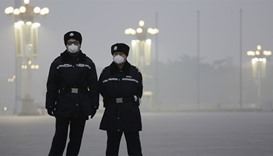 Policemen wear protective masks at the Tiananmen Square as choking smog continues to blanket Beijing