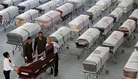 Funeral workers prepare a coffin with the remains of a victim who died when the plane carrying Brazi