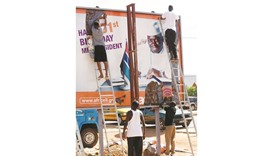 People begin removing an election poster for Jammeh in Broussbi, Gambia.