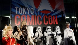 People dressed in costumes pose for a photograph during an opening ceremony of Tokyo Comic Con