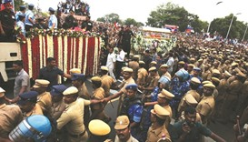 Supporters of Jayalalithaa crowd around the vehicle carrying her body during her funeral procession