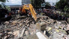 Rescue workers use heavy equipment to search for victims in a collapsed building following an earthq