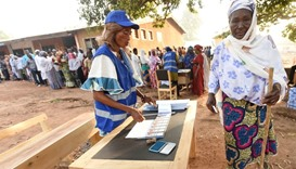 A woman prepares to vote for the presidential election at a polling station in Bole district, Ghana