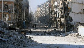 Syrians walk over the rubble as they flee clashes between regime forces and rebels in the Tariq al-B