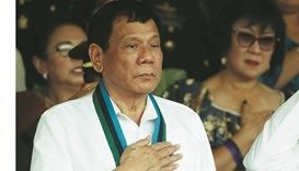 President Rodrigo Duterte stands to attention during the singing of Philippine national anthem at a