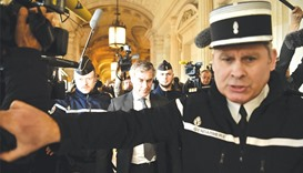 Gendarmes escort Cahuzac as he leaves the Paris courthouse following his tax fraud and money launder