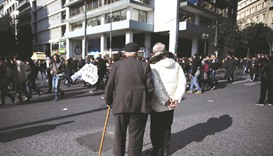 Two elderly men look at protesters marching during a demonstration in Athens marking a 24-hour gener
