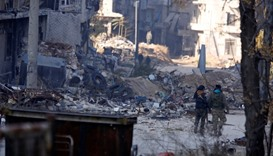 Forces loyal to syria's President Bashar al-Assad walk past damaged buildings in a government held a