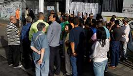 People check a list at a polling station during a nationwide election for new mayors, in Caracas