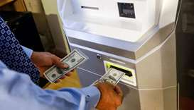 A man feeds money into a Bitcoin ATM at the Bitcoin Center NYC in New York, U.S. on November 27, 201
