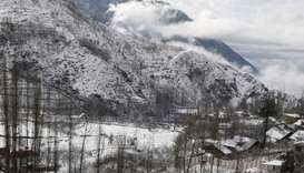 A Kashmiri villager clears snow from the roof of a house following fresh snowfall on the outskirts o