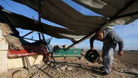 A Palestinian man inspects a militant target that was hit in an Israeli airstrike in the southern Ga