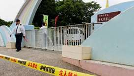A Japanese policeman stands guard at the entrance gate of the elementary school in Ginowan, Okinawa