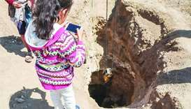 Zahara Taleb watches an unexploded bomb being removed from her father's farmland