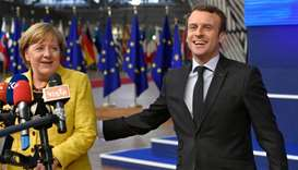 Germany's Chancellor Angela Merkel and France's President Emmanuel Macron answer the press as they a