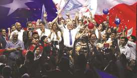 Chilean presidential candidate Sebastian Pinera waves to the crowd, surrounded by his family and sup