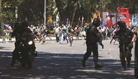 Protesters rush towards Argentine policemen outside the Congress in Buenos Aires, Argentina.