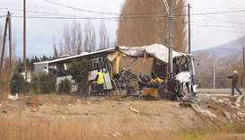 Towing service workers stand next to the wreckage of school bus in Millas, near Perpignan, southern