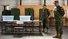Chilean soldiers stand guard at a polling station at the Amunategui highschool in Santiago