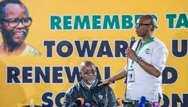 South Africa's ruling African National Congress (ANC) spokesperson Zizi Kodwa (R) gives a speech nex