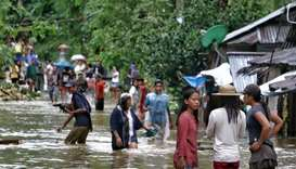 Villagers wade through a flooded street in Brgy Calingatngan, in Borongan, on easterm Samar in centr