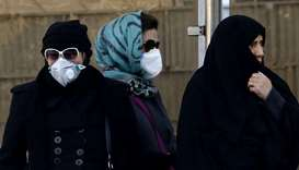 Iranian women wear face masks at a bus stop in Tehran as heavy pollution hit new highs in the capita