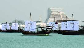 The dhows at Doha Corniche decorated with sails imprinted with portraits of His Highness the Emir Sh