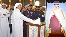 The portrait of His Highness the Emir Sheikh Tamim bin Hamad al-Thani (R) is being unveiled by HE th
