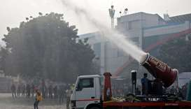 "A man operates an ""anti-smog gun"", a machine that sprays atomised water into the air to reduce pollu"