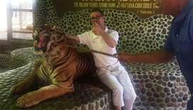 A tourist (C) poses with a roaring tiger being prodded by a Pattaya zoo staff.
